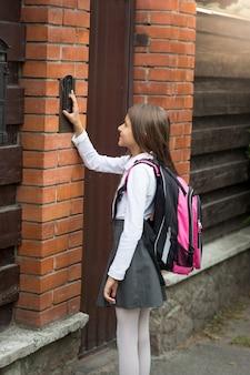 Portret van een mooi meisje in schooluniform dat op de intercomknop drukt