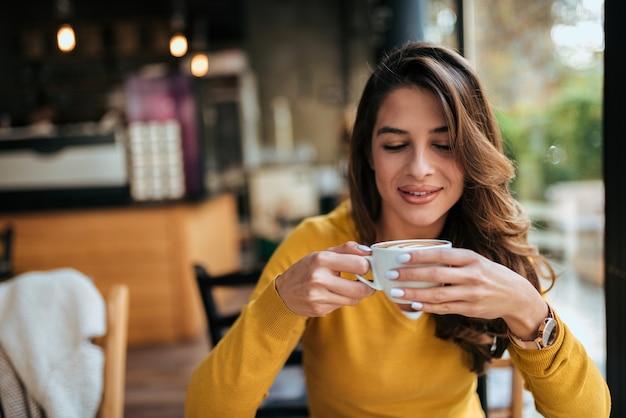 Portret van een mooi meisje kopje koffie drinken.