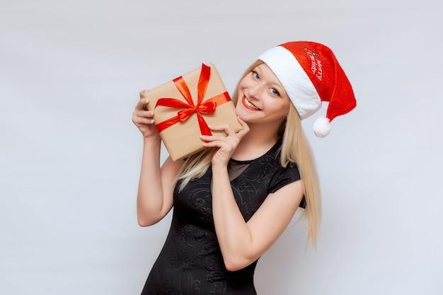Portret van een mooi meisje met een geschenkdoos in haar handen in een kerstmuts