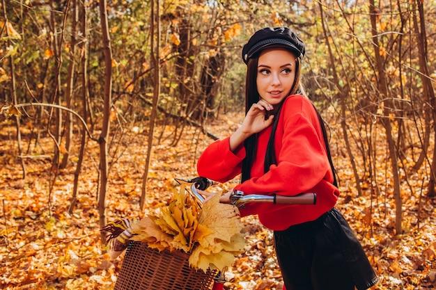 Portret van een mooi meisje met een rode fiets in het herfstbos