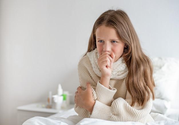 Portret van een mooi meisje met een temperatuur zit op het bed en hoest