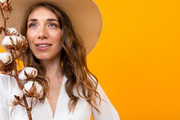 Portret van een mooi meisje met een zomerhoed met een twijg van katoen op een geel