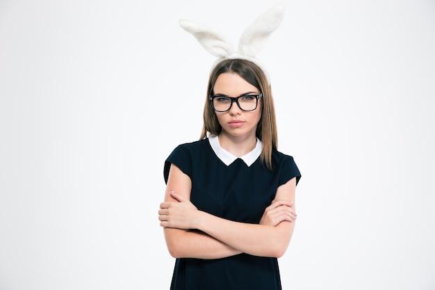 Portret van een mooi meisje met konijnenoren die zich met geïsoleerde wapens gevouwen bevinden