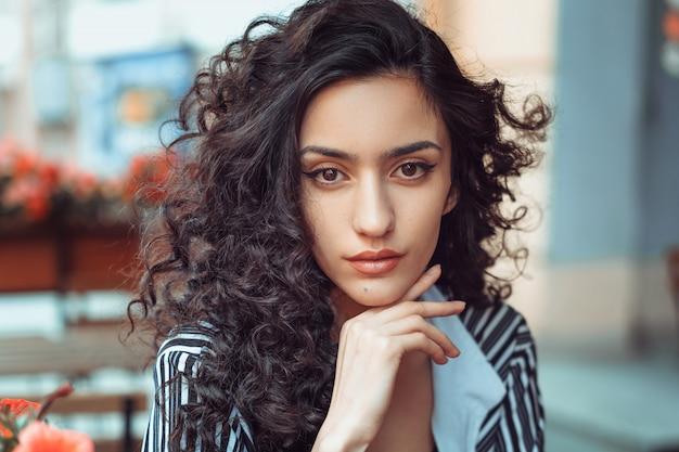 Portret van een mooi meisje met krullend haar op straat