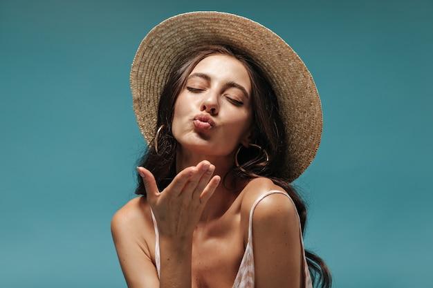 Portret van een mooi meisje met lang haar in moderne oorbellen en een coole hoed met brede rand die kus blaast met gesloten ogen op blauwe muur