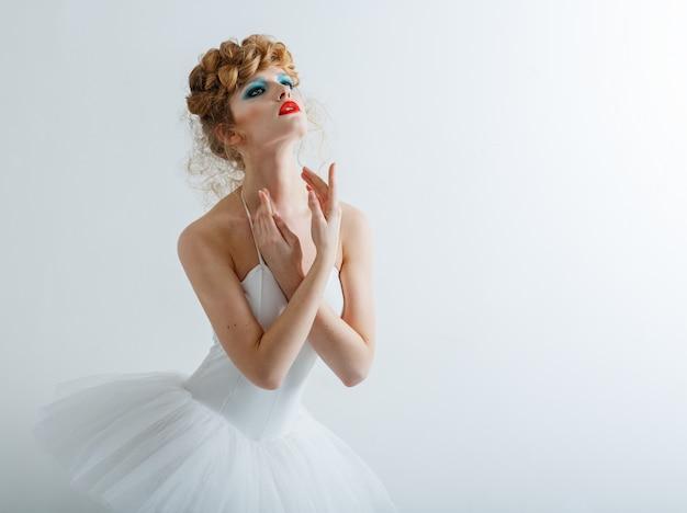 Portret van een mooi meisje met mode make-up rode lippen, stijlvol kapsel. in balletjurk.