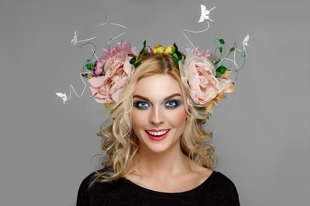 Portret van een mooi meisje met rode lippen en blauwe ogen met kroon van bloemen in blond krullend haar