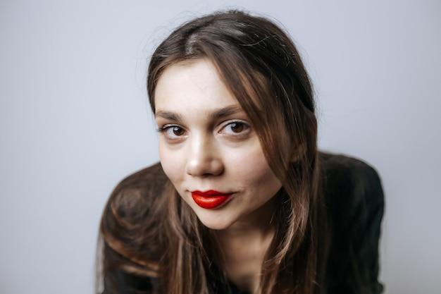 Portret van een mooi meisje met rode lippen, grote ogen en donker lang haar