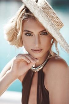 Portret van een mooi meisje, model in een zwembroek en een hoed met brede rand