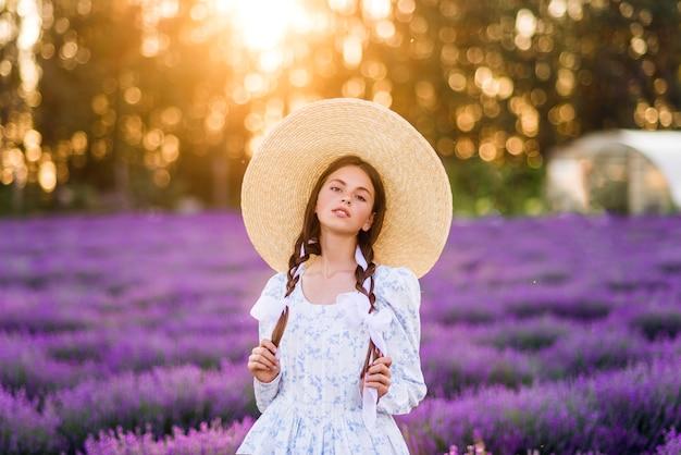 Portret van een mooi meisje op een lavendelachtergrond. een jong model. zomerfoto in de zon