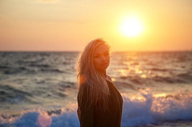 Portret van een mooi meisje op het strand bij zonsondergang.