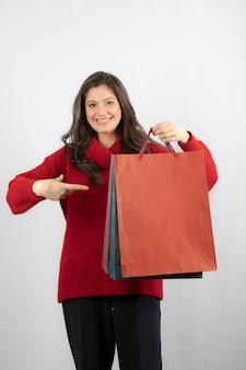 Portret van een mooi meisje wijzend op boodschappentassen geïsoleerd over witte muur.