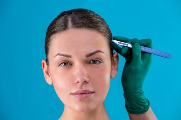 Portret van een mooi meisjesclose-up, met vlotte huid, handen die een scalpel in het gezicht met handschoenen houden. conceptschoonheid, jeugdbehoud, plastische chirurgie, gezondheid.