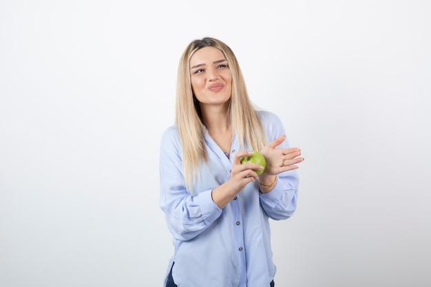 Portret van een mooi meisjesmodel dat staat en een groene verse appel vasthoudt.