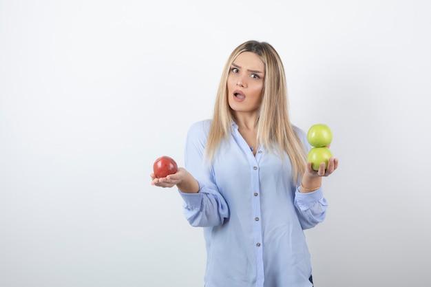 Portret van een mooi meisjesmodel dat staat en verse appels vasthoudt.