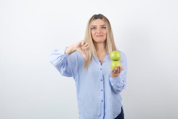 Portret van een mooi meisjesmodel dat verse appels houdt en een duim naar beneden laat zien.