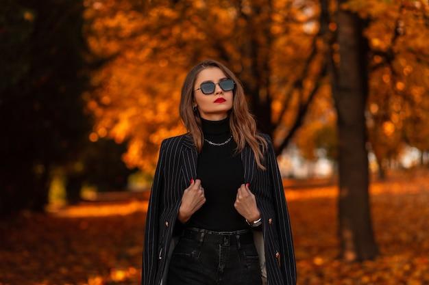 Portret van een mooi modieus meisje met zonnebril in een mode zwart pak met een blazer en een trui loopt in het park met kleurrijk gouden gebladerte
