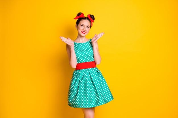 Portret van een mooi, mooi vrolijk meisje met een groenblauwe korte gestippelde jurk die met de handpalmen klapt, geïsoleerd over een felgele kleurachtergrond