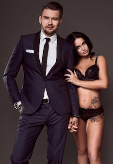 Portret van een mooi paar: brutale man in elegant pak en sexy meisje met een tatoeage in lingerie op grijze achtergrond