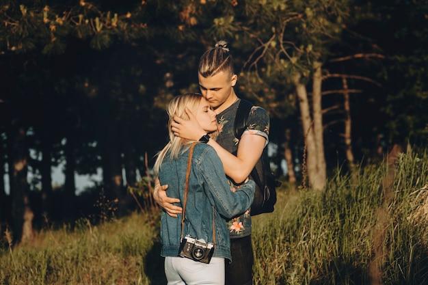Portret van een mooi paar omarmen tegen een bos terwijl het meisje haar hoofd op de borst van haar vriendje met gesloten ogen leunt terwijl hij naar haar kijkt, buiten tijdens het reizen.