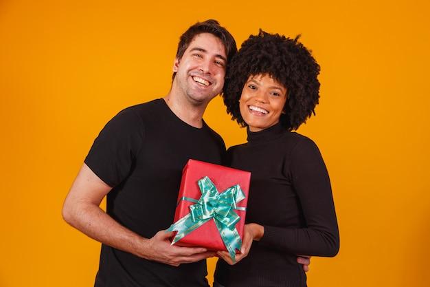 Portret van een mooi paar op geel met een geschenk