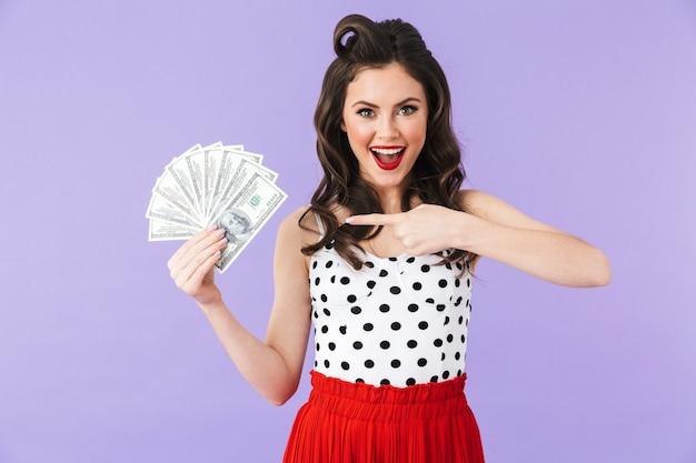 Portret van een mooi pin-upmeisje met heldere make-up die geïsoleerd staat over een violette muur en geldbankbiljetten toont