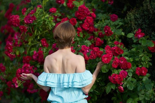 Portret van een mooi roodharigemeisje gekleed in een witte lichte kleding op een achtergrond van bloeiende rozen