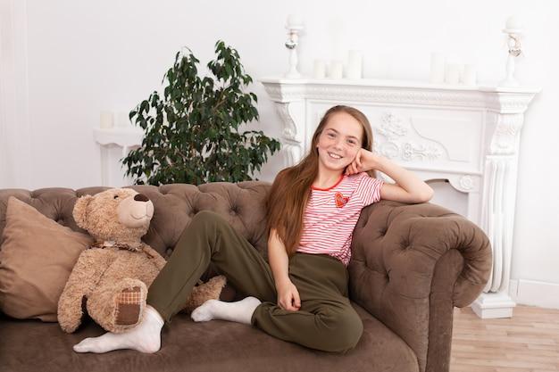 Portret van een mooi roodharigetienermeisje. leuke en meisjeszitting op de bank, het glimlachen en het kijken