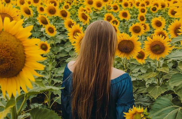 Portret van een mooi, schattig, sexy meisje in een blauwe jurk met bloemen van een zonnebloem. emotie van plezier, vrijheid concept, levensstijl. hij staat met zijn rug met lang haar.
