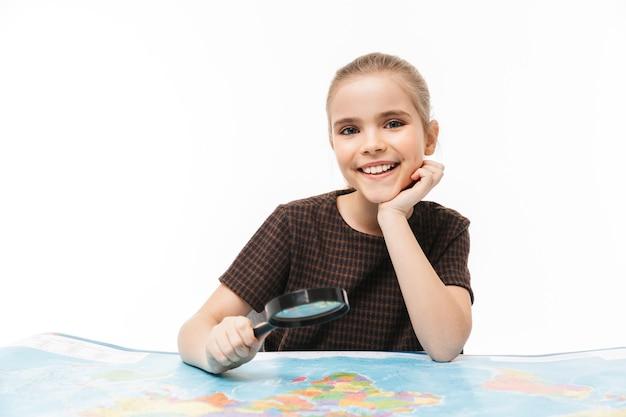 Portret van een mooi schoolmeisje dat door een vergrootglas naar de wereldkaart kijkt terwijl ze aardrijkskunde studeert op school, geïsoleerd over een witte muur