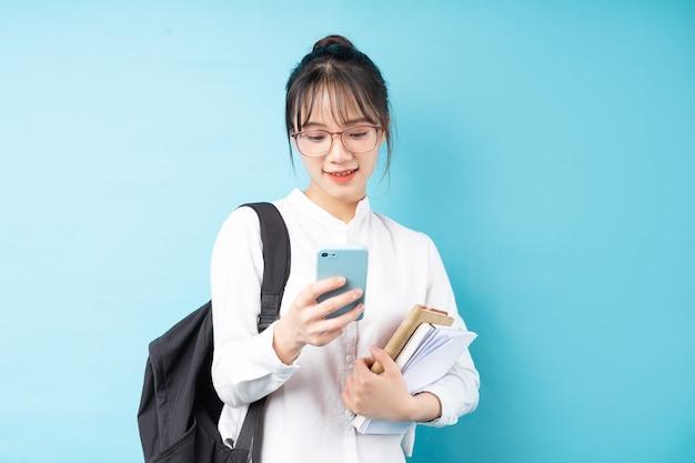 Portret van een mooi schoolmeisje op een blauwe achtergrond
