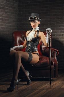 Portret van een mooi steampunkmeisje in lingerie en kousen die in oude leunstoel zitten.
