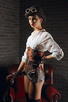 Portret van een mooi steampunkmeisje in lingerie en kousen, hoed en bril.