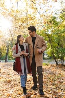 Portret van een mooi stel dat afhaalkoffie drinkt uit papieren bekers en elkaar aankijkt tijdens het wandelen in het herfstpark