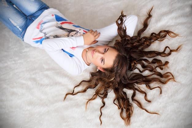 Portret van een mooi tienermeisje dat op de vloer met haar lang golvend haar ligt