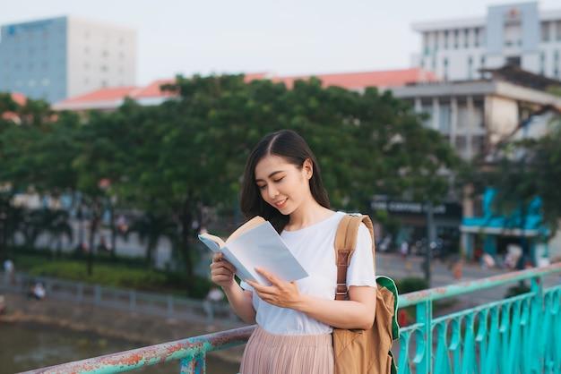 Portret van een mooi vietnamees meisje dat staat en een boek leest in de wind met een wazige stadsachtergrond gelukkige lezer op de universiteit.