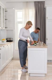 Portret van een mooi volwassen stel dat samen kookt, een gelukkige senior vrouw die ontbijt kookt in het wit