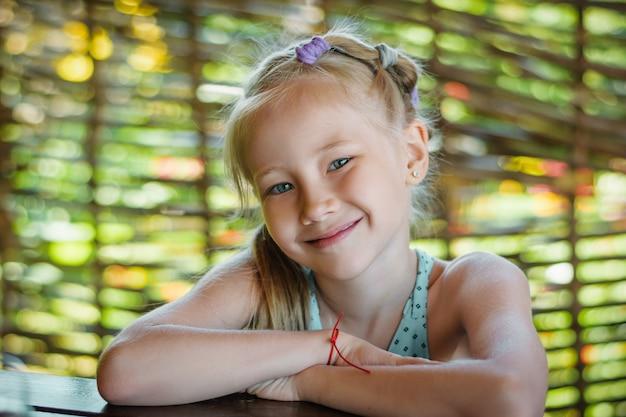 Portret van een mooi vrolijk meisje op een achtergrond van een hek van takken.