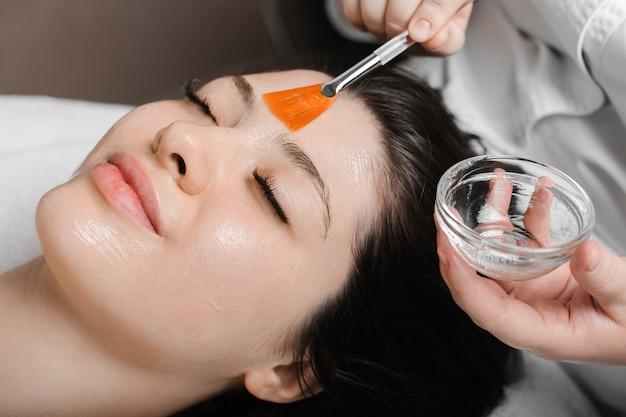 Portret van een mooi vrouwelijk gezicht met gesloten ogen close-up gezichtsmasker anti acne doen door een schoonheidsspecialist in een wellness-centrum.