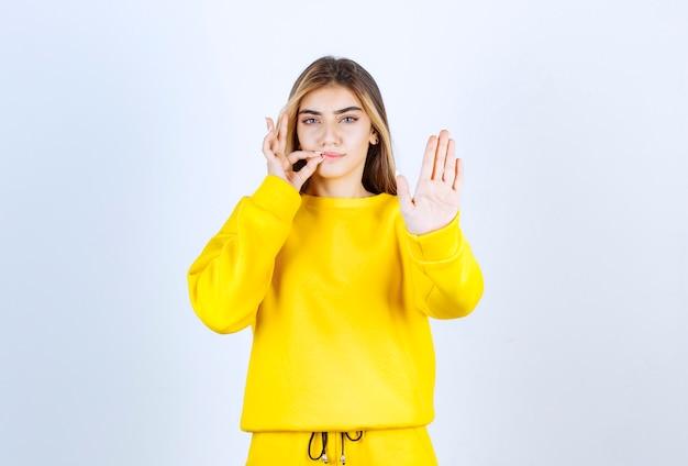Portret van een mooi vrouwenmodel dat staat en nummer vijf met de hand toont