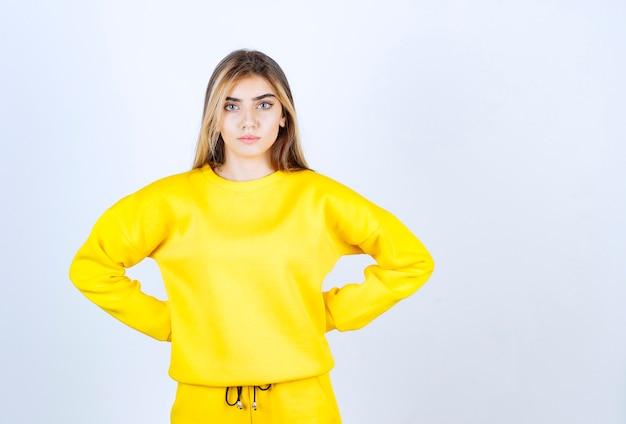 Portret van een mooi vrouwenmodel dat staat en poseert in een geel t-shirt