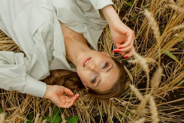 Portret van een mooie aangename vrouw die haar haar vasthoudt met haar hand, die door de wind wordt geblazen. ze staat op het dak en lacht.