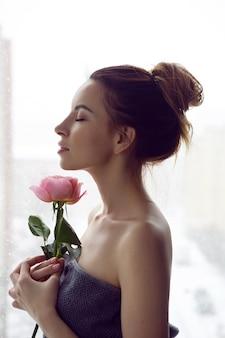 Portret van een mooie aantrekkelijke vrouw in een grijze handdoek in de badkamer met een rode roos
