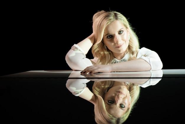 Portret van een mooie actrice in de buurt van een witte piano.