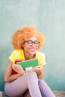 Portret van een mooie afrikaanse student met kleurrijke boeken op de groene muurachtergrond