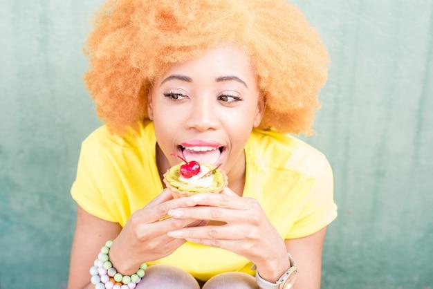 Portret van een mooie afrikaanse vrouw in geel t-shirt met een zoet dessert met kers op de groene achtergrond