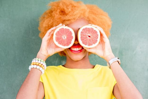 Portret van een mooie afrikaanse vrouw met grapefruitplakken op de groene muurachtergrond
