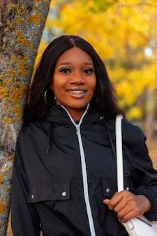 Portret van een mooie afro-amerikaanse jonge vrouw met een glimlach in een modieus zwart casual jasje in de buurt van een boom in een park met helder gouden herfstgebladerte