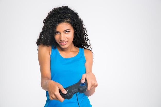 Portret van een mooie afro-amerikaanse vrouw die in videogame met joystick speelt die op een witte muur wordt geïsoleerd