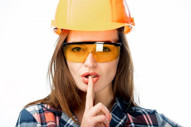 Portret van een mooie architectenvrouw die in veiligheids oranje helm en beschermende glazen gebaar van stilte maakt door haar vinger.